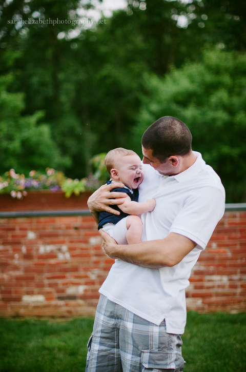 Dad and baby in front of brick wall at Smithville Mansion