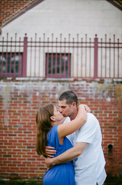 Couple in front of brick wall at Smithville Mansion