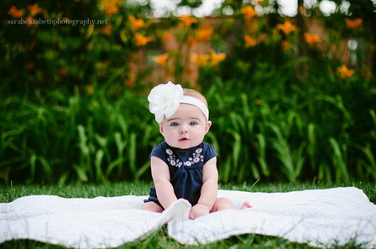 Baby in front of yellow flowers at Smithville Mansion